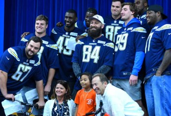 Principal Kathleen Gallagher, Bill Polokov and Chargers players pose with a girl who won a bike. Photo by Chris Stone