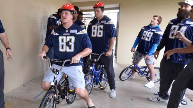 Charger players line up to ride in free bikes for kids, paid for my the Chargers organization. Photo by Chris Stone