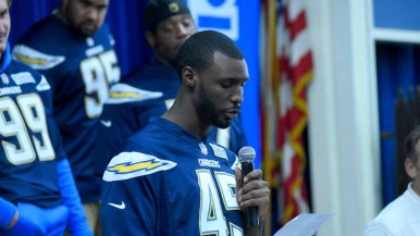 Chargers player Asante Cleveland reads the essay of one of the winners. Photo by Chris Stone