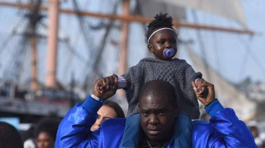 A young participant gets a ride in the annual Martin Luther King Parade down Harbor Drive. Photo by Chris Stone