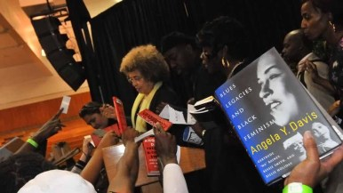 A supporter holds up an Angela Davis book in the hopes of getting it autographed. Photo by Chris Stone