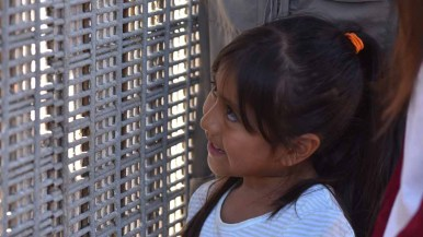 Kimberly, 6, daughter of Jannet Lorenzo, smiles at her grandmother, Reynea Mosso, through the border fence. Photo by Chris Stone