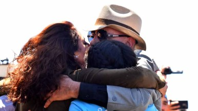 Jannet Fernandez Vargas and her daughter, Jasmine, embrace her father, Javier. Photo by Chris Stone