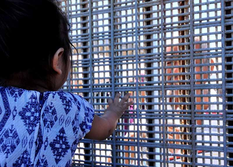 A toddler on the U.S. side of the border fence reaches for a relative on the other side