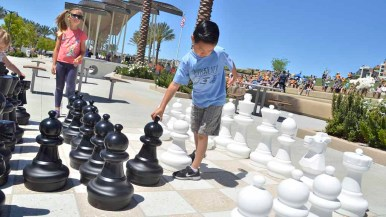 Children play on large chess board at the opening of Civita Park in Mission Valley. Photo by Chris Stone