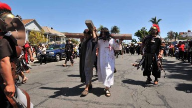 Actors portraying Jesus and Simon of Cyrene carry a cross through the streets of Barrio Logan. Photo by Chris Stone