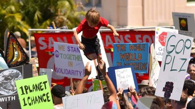 Young boy is tossed in the air after People's Climate March San Diego. Photo by Ken Stone