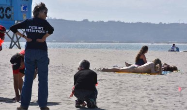 Protesters set up staging area by the Hotel del Coronado as young women sunbathe nearby. Photo by Chris Stone