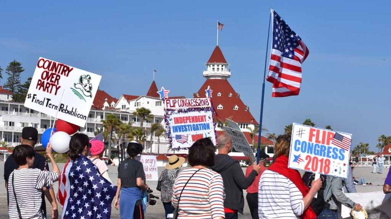 Protesters walk along the beach in front of the Hotel del Coronado to oppose Trump administration policies. Photo by Chris Stone