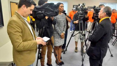 The Union-Tribune's Josh Stewart listens as KPBS crew quizzes Mickey Kasparian after news conference. Photo by Ken Stone