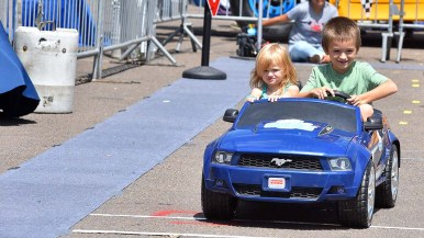 Britta McNealy and her brother Peyton take a spin in a mini electric car