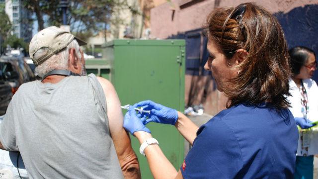 Nurse gives hepatitis A vaccine to homeless man