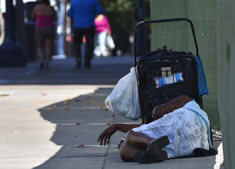 A homeless woman sleeps on the sidewalk in downtown San Diego.