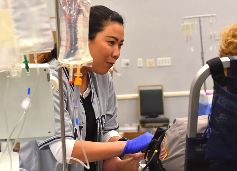 A nurse wearing a Padres jersey helps a donor during the blood drive.