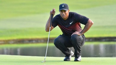 Crouching Tiger Woods studies for a putt on the 18th green at Torrey Pines South Course.