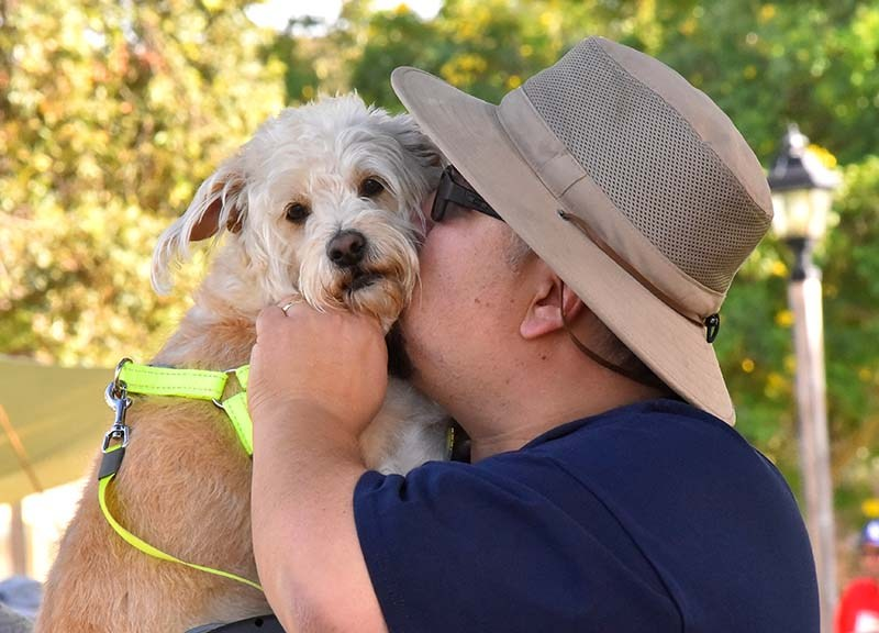 A man kisses his dog prior to the Blessing of the Animals event.