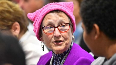 A delegate wearing a pink pussy hat talks to a fellow delegate.