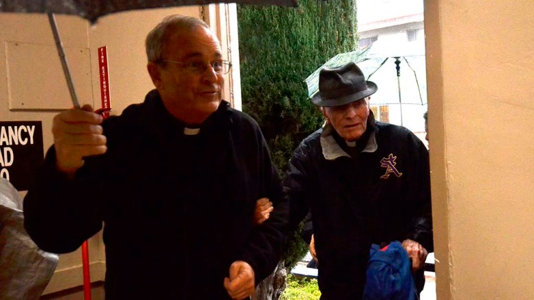 Our Lady of Guadalupe Pastor, the Rev. John Auther, S.J. , escorts the Rev. Richard Brown for his farewell party.