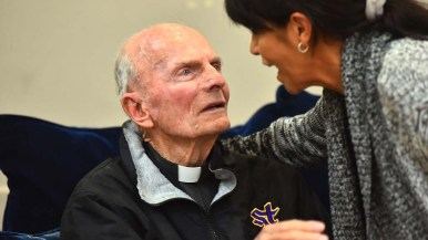 The Rev. Richard Brown listens intently as a parishioner thanks him for his help.