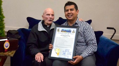 City Councilman David Alvarez shows the City Council Proclamation naming March 10 Father Richard Brown Day in San Diego.