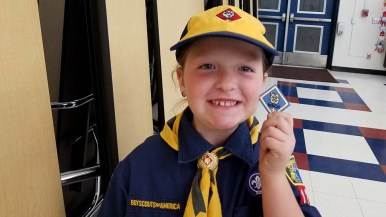 Laura Hutto, the first girl in San Diego County to join the Cub Scout, beams upon receiving her first patch.