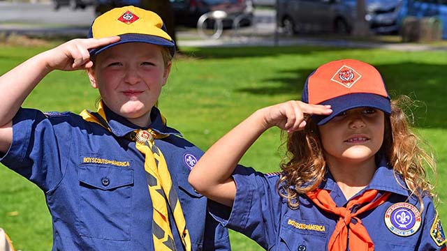 Laura Hutto (left) and Evangelina Rodgers practice their Cub Scout salute