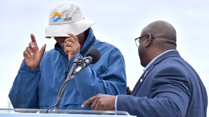 Willie Banks wears sun hat with ANOC World Beach Games logos on overcast day at Mission Beach. Organizing committee chair Vincent Mudd is at right.