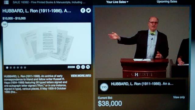 """John Hays gestures as winning """"hammer price"""" bid of $38,000 is registered."""