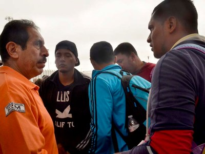 Refugees gather early in the morning to consult a member of the Mexican Institute of Migration about their place in line.