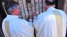 Associate San Diego Bishop John Dolan and Bishop Robert McElroy stand at the Mexican border fence.