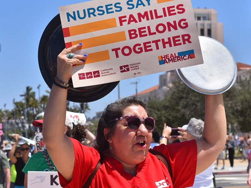 A nurse shows her support for keeping immigrant families united during a march near Waterfront Park in San Diego.