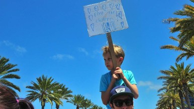 A young boy holds his handmade sign while on the shoulders of a man during the march.