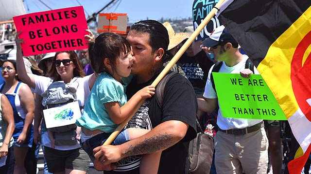 A father kisses his daughter during a march in downtown San Diego.