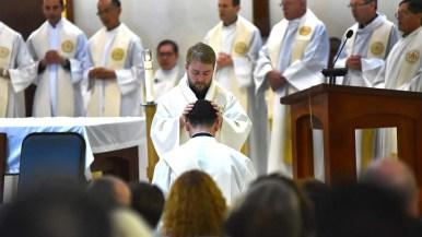 A Jesuit lays his hands on O. Alejandro Baez-Gonzalez during the ordination.
