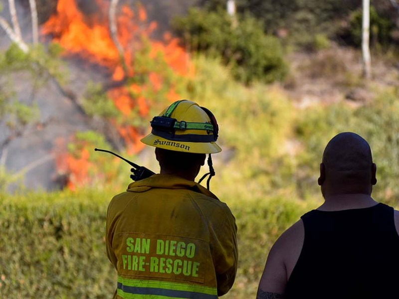 Flames are watched by a San Diego firefighter and a resident, looking across a culvert.