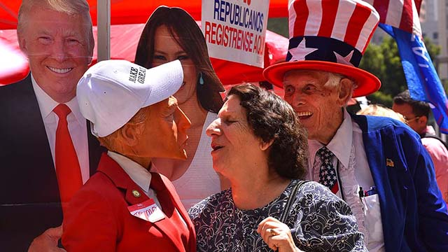 A new U.S. citizen shares a moment with a woman wearing a Donald Trump mask outside Golden Hall.