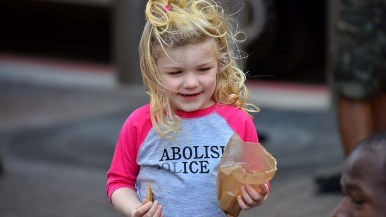 Adeline, 3, eats a snack during a protest in front of the James Carter and Judith Heed courthouse downtown.