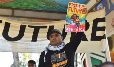 An activist displays the rally's poster at Chicano Park.