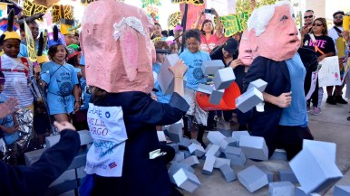 Children break through blocks that were set up in Chicano Park by effigies of Trump Administration officials.