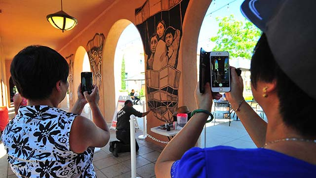 Two passersby take time to photograph two of the murals at Liberty Station.