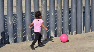 A little girl plays with a ball on the Mexican side of the U.S.-Mexico border.