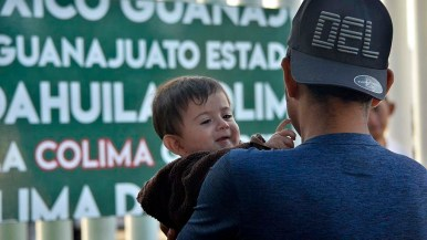 A baby is held was people wait from entrance in the U.S.at the San Ysidro Port of Entry.