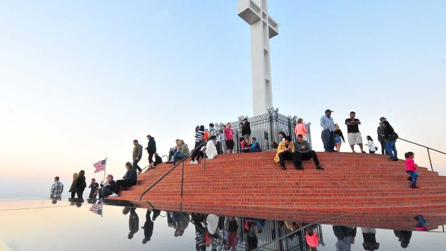 Visitors to Mt. Soledad National Veterans Memorial on Veterans Day are reflected on a wall.