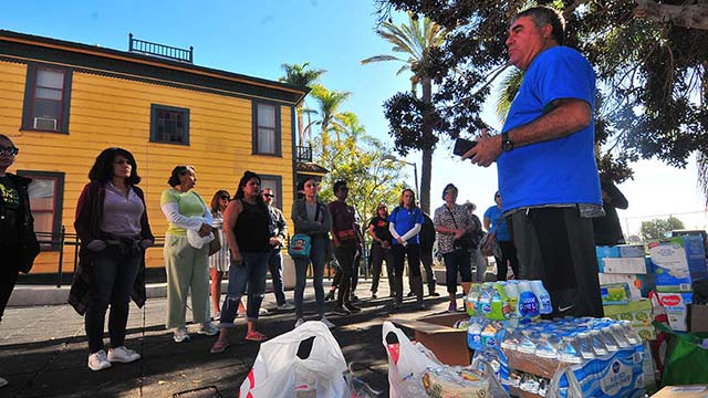 Enrique Morones, founder and director of Border Angels, talks to volunteer going to the Tijuana shelters to distribute donations.