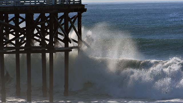 High surf pounds Crystal Pier, which was closed beyond the cottages.