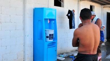 Migrants at El Barretal gather water at a communal water spout.