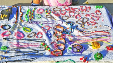 Beads and crafts are laid out by a migrant to be sold to visitors.