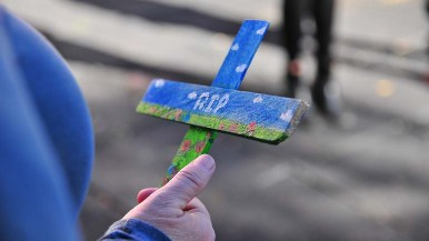 A volunteer holds a cross commemorating migrants who have died in the immigration process.