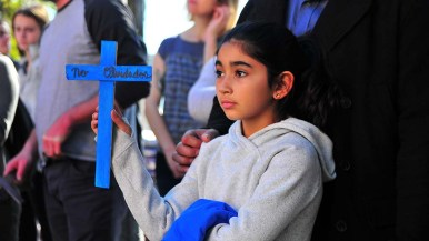 A young volunteer holds a not forgotten sign at a gathering at Border Angels headquarters before the Caravan of Love began.
