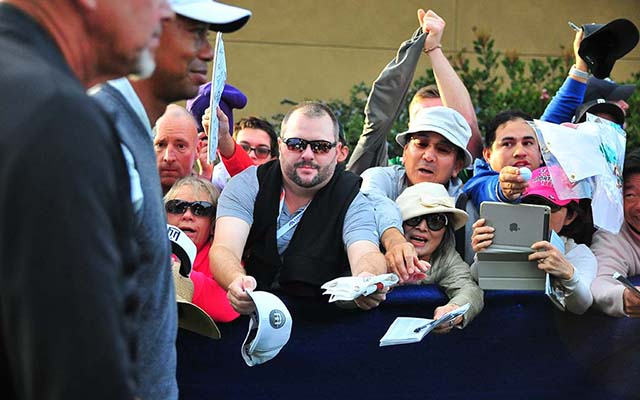Tiger Woods walks past beseeching autograph-seekers at Farmers Insurance Open.